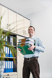 Young businessman carrying pile filing folders