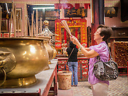 20 DECEMBER 2012 - KUALA LUMPUR, MALAYSIA: A woman prays in the Sin Sze Si Ya Temple, also known as the Sze Yah Temple, in Kuala Lumpur, Malaysia. The Sin Sze Si Ya Temple is the temple built by Yap Ah Loy, one of the Chinese founders of Kuala Lumpur. It is built according to Feng Shui principles and as such is not in alignment with other buildings in the neighborhood or the city grid. It is one of the oldest Chinese temples in Kuala Lumpur.   PHOTO BY JACK KURTZ