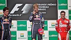 O piloto alemão de Fórmula Sebastian Vettel (C) comemora a vitória com o seu companheiro da equipe Red Bull, o australiano Mark Webber (E) e o piloto espanhol Fernando Alonso (D) durante  a cerimônia no pódio após vencer o Grande Prêmio de F1 do Brasil, no Autódromo de Interlagos em 07 novembro de 2010, em São Paulo. Webber chegou em segundo lugar e Alonso ficou em terceiro na corrida. FOTO: Jefferson Bernardes/Preview.com