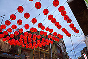 Red Chinese lanterns hang above a market in the early evening. Lanterns such as these are a common site, used as both a source of light and a blessing for good fortune.