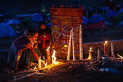 A woman and a child lights candles at night next to a banner that identifies his comparsa during the celebration of the Lord of Qoyllur Rit'i (The Lord of the Shining Snow), in Cusco, Peru.