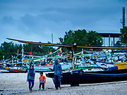 03 AUGUST 2017 - KUTA, BALI, INDONESIA: A family walks past fishing canoes along Jimbrana Beach in Kuta. The beach is close to the airport and a short drive from other beaches in southeast Bali. Jimbrana was originally a fishing village with a busy local market. About 25 years ago, developers started building restaurants and hotels along the beach and land prices are rising. The new emphasis on tourism is changing the nature of the area but the fishermen are still busy very early in the morning.     PHOTO BY JACK KURTZ