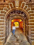 Redhead lady walks through arches at Sao Tiago (Saint Tiago) Fortress, Funchal, Madeira.