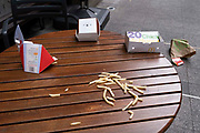 Discarded chips French Fries and McDonalds packaging lie on the ground and on a cafe table in central London, on 26th September 2021, in London, England.