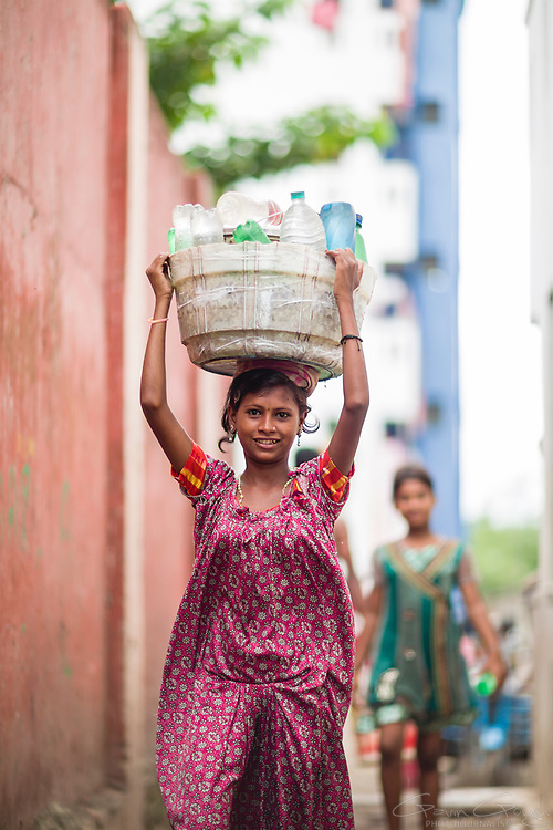 A young woman carrying plastic bottles filled with water in a bucket balanced upon her head, Tangra slum, Dhipi, Kolkata, India
