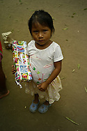 Over the last quarter-century, a few Embera families pushed further North of Darien, settling in the jungles bordering the Ipeti? River -- a scant two-hour journey from cosmopolitan Panama City. Embera communities are scattered in this border wilderness. Pictured: Children open gifts after a solidary Christmas caravan.