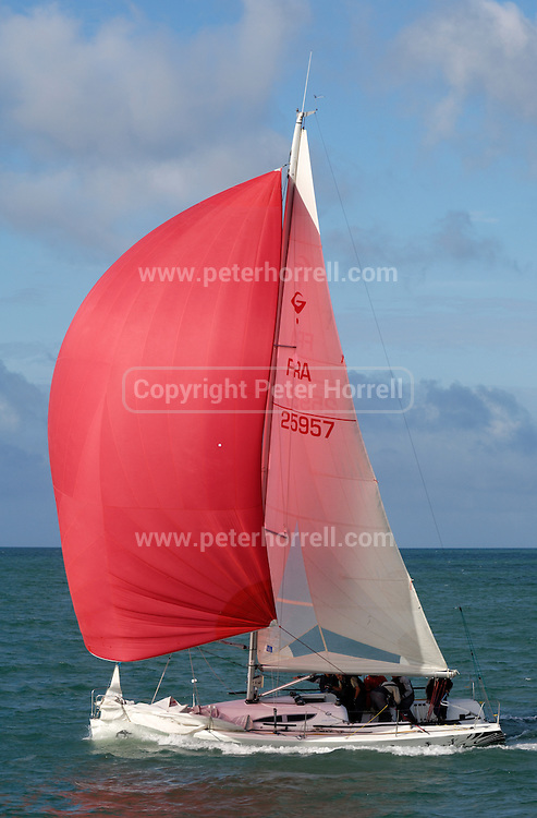 France, La Rochelle, 9 October 2009: Yacht, FRA 25957, with red spinnaker on calm sea with blue sky and cloudy background. Photo by Peter Horrell / http://peterhorrell.com.