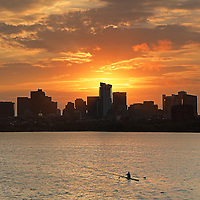 Early morning sunrise skyline photography image of Beacon Hill and the Massachusetts State House with newly constructed Millennium Tower in Boston. A single scull with one rower working out hard and pushing through a morning fitness workout rowing upstream in the orange reflection of the morning sky on the Charles River.<br /> <br /> Photos of Boston are available as museum quality photography prints, canvas prints, acrylic prints or metal prints. Fine art prints may be framed and matted to the individual liking and decorating needs:<br /> <br /> http://juergen-roth.pixels.com/featured/working-out-hard-juergen-roth.html<br /> <br /> All Boston skyline photos are available for digital and print image licensing at www.RothGalleries.com. Please contact me direct with any questions or request.<br /> <br /> Good light and happy photo making!<br /> <br /> My best,<br /> <br /> Juergen<br /> Prints: http://www.rothgalleries.com<br /> Photo Blog: http://whereintheworldisjuergen.blogspot.com<br /> Instagram: https://www.instagram.com/rothgalleries<br /> Twitter: https://twitter.com/naturefineart<br /> Facebook: https://www.facebook.com/naturefineart