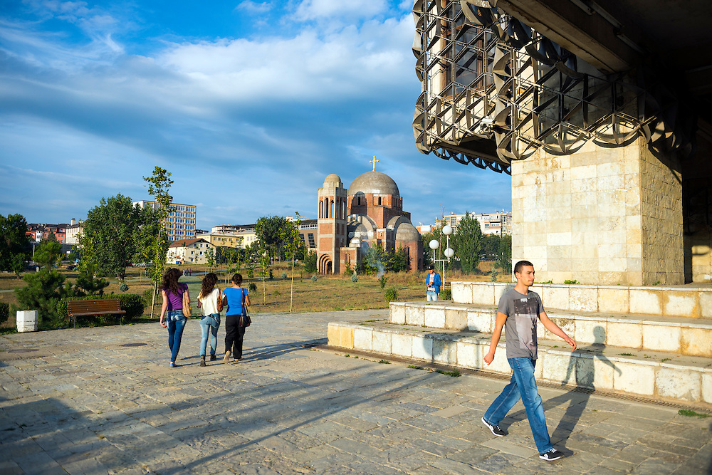 Young Kosovars walk past a corner of The National and University Library of Kosovo, located on the University of Pristina campus. In the background is the controversial Christ the Saviour Cathedral, an unfinished Serbian Orthodox Christian church whose construction began in 1995 but was never finished due to the Kosovo War. The fate of the building is contested.