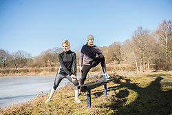 Man and woman doing stretching by frozen lake in forest