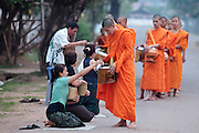 "12 MARCH 2009 -- VIENTIANE, LAOS:  Buddhist Monks in Vientiane, Laos, go about their ""Tak Bat,"" Lao for ""monks morning rounds."" The monks collect alms in the form of food from people who line their route. For the monks, it is the only food they get that day, for the people it's a chance to ""make merit."" Photo By Jack Kurtz"