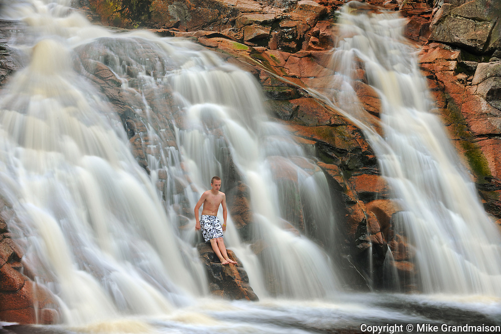 Boy in waterfall. Mary Ann Falls. MOdel released <br /> Cape Breton Highlands National Park<br /> Nova Scotia<br /> Canada