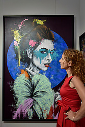 "© Licensed to London News Pictures. 06/10/2017. London, UK.  A woman views ""Yuansu"" by Fin Dac at the Moniker Art Fair, the world's biggest urban art fair, taking place at the Old Truman Brewery in East London from 5 to 8 October 2017.  The fair brings together the world's most influential new-contemporary and urban art galleries to show international artworks to Londoners. Photo credit : Stephen Chung/LNP"