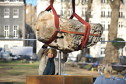 © Licensed to London News Pictures. 02/02/2012, London, UK. Sculptor Emily Young supervises the installation of her work 'The Metaphysics of Stone' in London's Berkley Square today (2nd February 2012).  The six stone heads were lifted in by two cranes. Photo credit : Stephen Simpson/LNP
