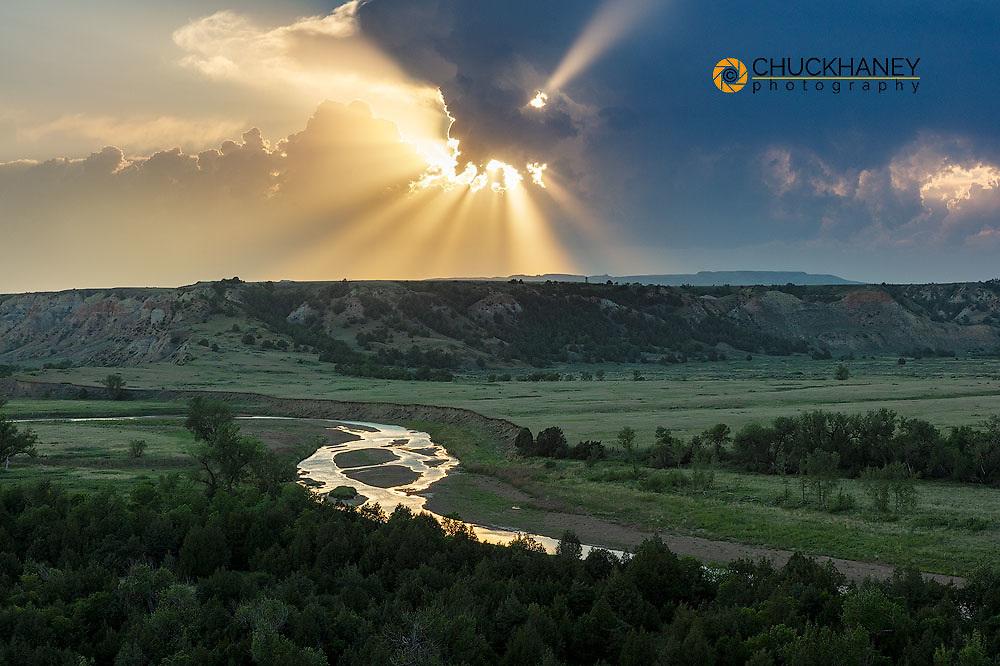Setting sun rays poke through thunderstorm clouds above the Little Missouri River in the Little Missouri National Grasslands, North Dakota, USA