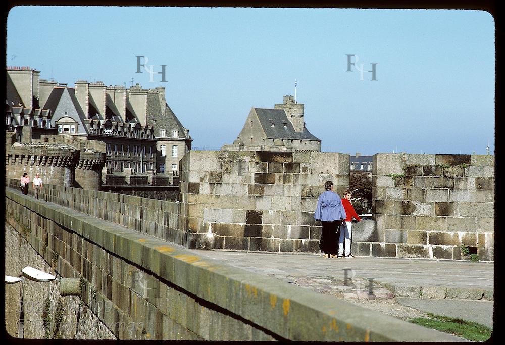 Tourists walk along the battlements of fortress city of Saint Malo and peek thru crenels. France