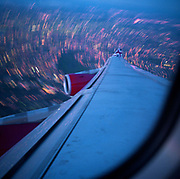 In mid-flight over Greater London, we see a passenger's view of a turning airliner's wing and the capital's dusk landscape below at a low altitude. As the starboard (right) wing dips, the Virgin Atlantic Airbus banks and a long exposure blurs the city lights below. A small curved portion of the passenger window, red engines and the Union Jack colours are seen. As aerodynamic design, the flying machine is a perfect gesture towards the conquest of flight, copied from the characteristics of a bird's anatomy. As art, the mere beauty of taking to the air and maintaining level, organised speed is so routine, we rarely look our from our window to marvel at how and why. Picture from the 'Plane Pictures' project, a celebration of aviation aesthetics and flying culture, 100 years after the Wright brothers first 12 seconds/120 feet powered flight at Kitty Hawk,1903.