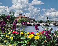 Flowers along the railing of the Illinois Street Bridge are the forground for a summer day picture of downtown St. Charles, IL.