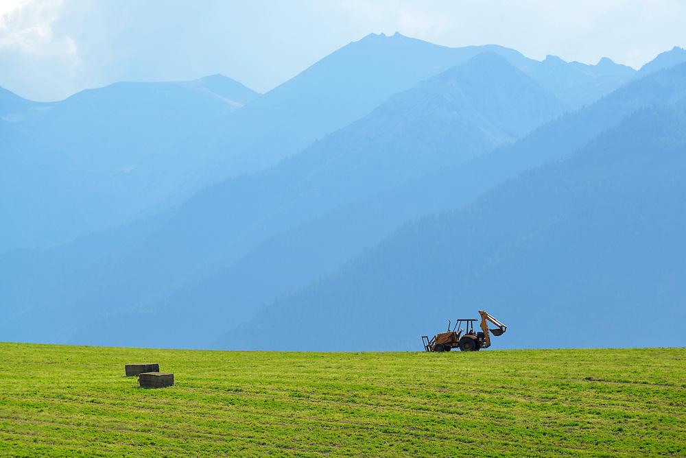 Backhoe parked on a hay field in Oregon's Wallowa Valley.