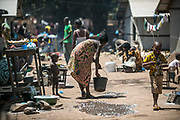 An IDP woman sprays water on a hot soil in Bangui, Central African Republic.