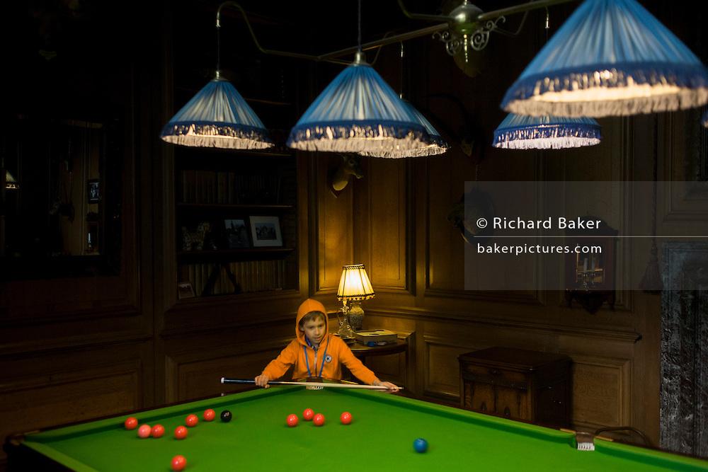 A young boy plays billiards in Avebury Manor.