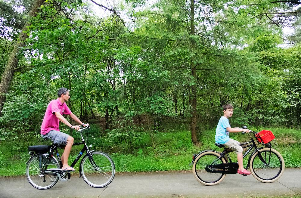 In Soest rijdt een man met zijn zoon op de fiets in de bossen.<br /> <br /> In Soest a man is cycling with his son in the forest.