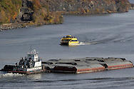 Fort Montgomery, NY - A tugboat pushes a barge down the Hudson River as a  New York Water Taxi boat on a fall foliage cruise heads upriver just south of the Bear Mountain Bridge on Nov. 2, 2008.