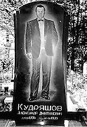 Dressed to kill: Gaudy tombstones of Russian gangsters depict them wearing designer suits with flash cars<br /> <br /> <br /> They used to spend their days collecting protection money, kneecapping those who would not pay up and planting explosives in the cars of their rivals.<br /> But now the only reminders of the gangsters that made up the Russian mobs in the 1990s are their tombstones with gaudy sketches of them etched into the granite. <br /> The men, who are casualties of the Russian business world and were relatively young when they were killed, are sculpted standing in designer suits and leather jackets.<br /> hey stare back at the onlooker, smiling or stern, as proud in death as when they were alive.<br /> Their graves are marked by life size headstones, where their images are expertly engraved into imported marble.<br /> On the edge of the Russian city of Yekaterinburg  lies the Shirokorechenskoye cemetery.<br /> This is the final resting place for mobster, Miklhail Kuchin, boss of the notorious Centralnaya gang who was gunned down aged 35 as he left his home. <br /> His gravestone shows him as thick-necked, dressed in a double breasted suit. and he is depicted clutching the keys to his beloved Mercedes 600.<br /> This, in a country where buying a Lada is beyond millions of people's pockets, working or not.<br /> Nearby are the graves of father and son gangsters Nikolai and Andrei Kravtsov, shot by contract killers as they drove in their Volvo in 1996. They were cut down at the ages of 44 and 22.<br /> Hefty gravestones commemorate the two men and between them a separate stone is dedicated to their precious car.<br /> On their tombs, some are depicted with their tattoos, or smoking cigarettes. <br /> Others are buried with their mobile phones so they can be kept up to date with the daily round of gangland shootings and beatings.<br /> In an enormous tomb-Oleg Vagin is buried alongside his three armed bodyguards, who couldn't draw their guns fast enough to save him when they were all massacred in 1992.<br /> ©exclusivepix