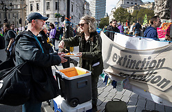 © Licensed to London News Pictures. 09/10/2019. London, UK. An Extinction Rebellion activist serves a plate of hot food in Trafalgar Square during a third day of protests in central London. The climate change group intend to blockade the Westminster area for two weeks to demand that the government takes immediate and decisive action on climate change. Photo credit: Peter Macdiarmid/LNP