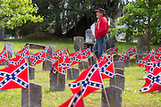 A Civil War re-enactor walks past rebel flags decorating grave markers of soldiers killed in the US Civil War during Confederate Memorial Day at Magnolia Cemetery April 10, 2014 in Charleston, SC. Confederate Memorial Day honors the approximately 258,000 Confederate soldiers that died in the American Civil War.