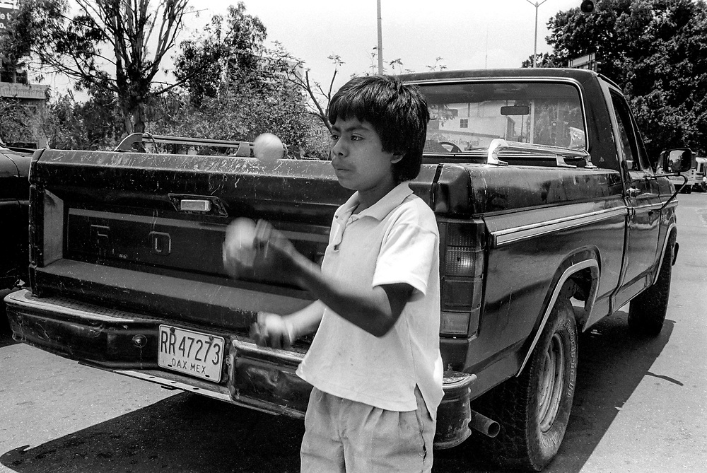 Street boy juggling in order to make money. Oaxaca, Mexico