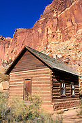 Morning light on the Fruita Schoolhouse under the colorful sandstone cliffs of the Waterpocket Fold in Fruita, Capitol Reef National Park, Utah