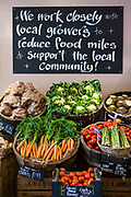 "A variety of locally produced fruit and vegetables on display in a greengrocer and connivence shop in Wadebridge, North Cornwall, United Kingdom. The blackboard informs that the store works ""closely with local growers and suppliers to reduce food miles and support the local community""."