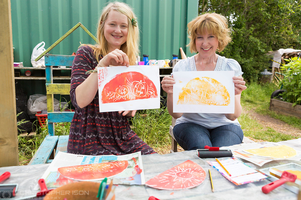 20140601 Free for editorial use image<br /> <br /> Halifax colleagues in Bournemouth are proud to give extra back to their local community by hosting their Big Lunch event on Sunday 01 June 2014.<br /> <br /> Christine Johnson and daughter Lauren enjoying the activities during The Big Lunch at the New Leaf Allotment in Bournemouth. <br /> <br /> For more information please contact: Catherine Eastham on 020 3697 4304<br /> <br /> If you require a higher resolution image or you have any other onEdition photographic enquiries, please contact onEdition on 0845 900 2 900 or email info@onEdition.com<br /> This image is copyright the onEdition 2014©.<br /> This image has been supplied by onEdition and must be credited onEdition. The author is asserting his full Moral rights in relation to the publication of this image. Rights for onward transmission of any image or file is not granted or implied. Changing or deleting Copyright information is illegal as specified in the Copyright, Design and Patents Act 1988. If you are in any way unsure of your right to publish this image please contact onEdition on 0845 900 2 900 or email info@onEdition.com