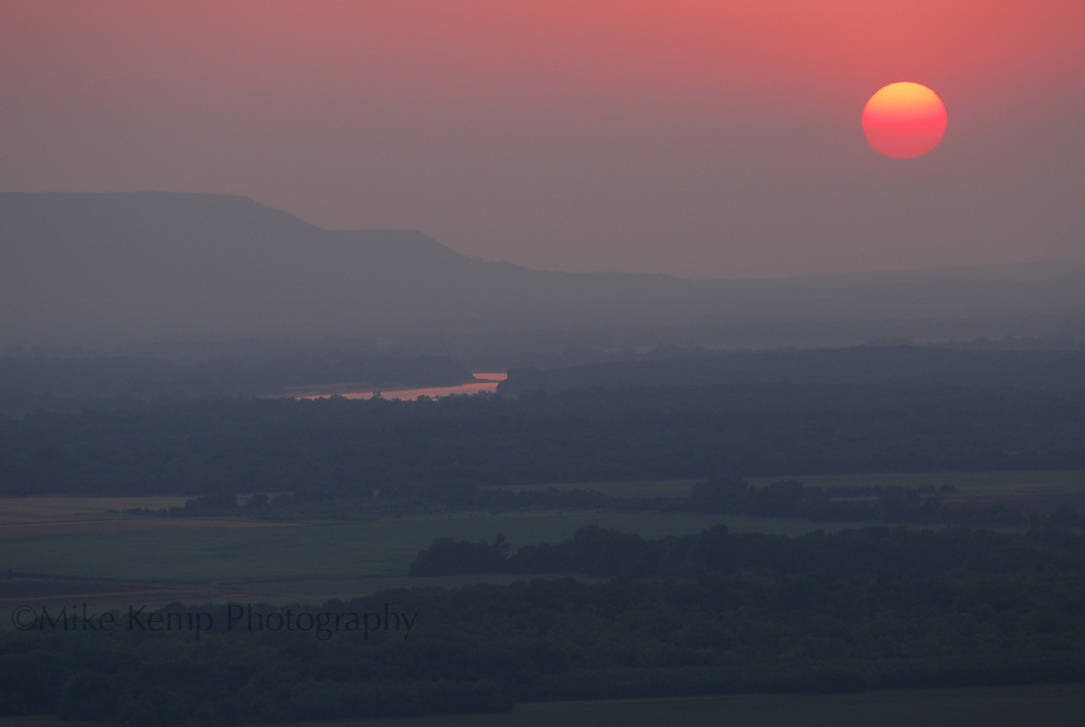 The sun sets over the Arkansas River Valley near Petit Jean State Park.