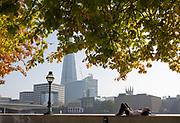 An office worker in the City of London - the capital's financial district - enjoys late summer temperatures on Hanseatic Walk that overlooks the Shard skyscraper, London Bridge and the Thames river, on 10th October 2018, in London, England.