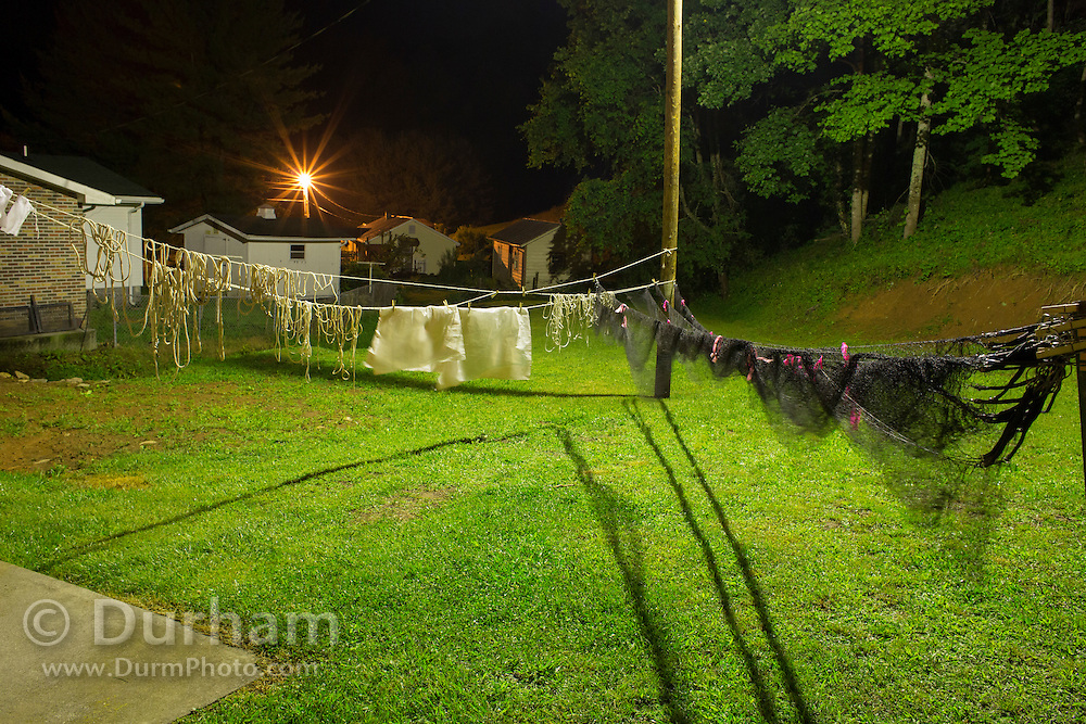 Bat researchers keep odd hours. Bat researcher Vanessa Rojas and her crew dry mist nets in yard at night in back of the little house they rent during field season.