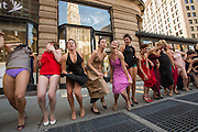The women dancers pull up their skirts to show their panties.