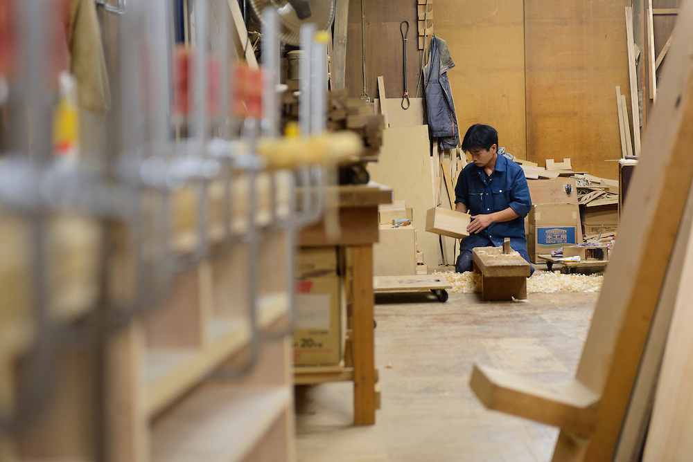 An artisan working on a chest of drawers, Iwayado Tansu Seisakujo, Oshu City, Iwate Prefecture, Japan, July 18, 2013. Iwayado Tansu chests of drawers have been made in the city of Oshu since the 1780s. They are noted for their fine lacquer finish and finely-wrought metalwork fittings.