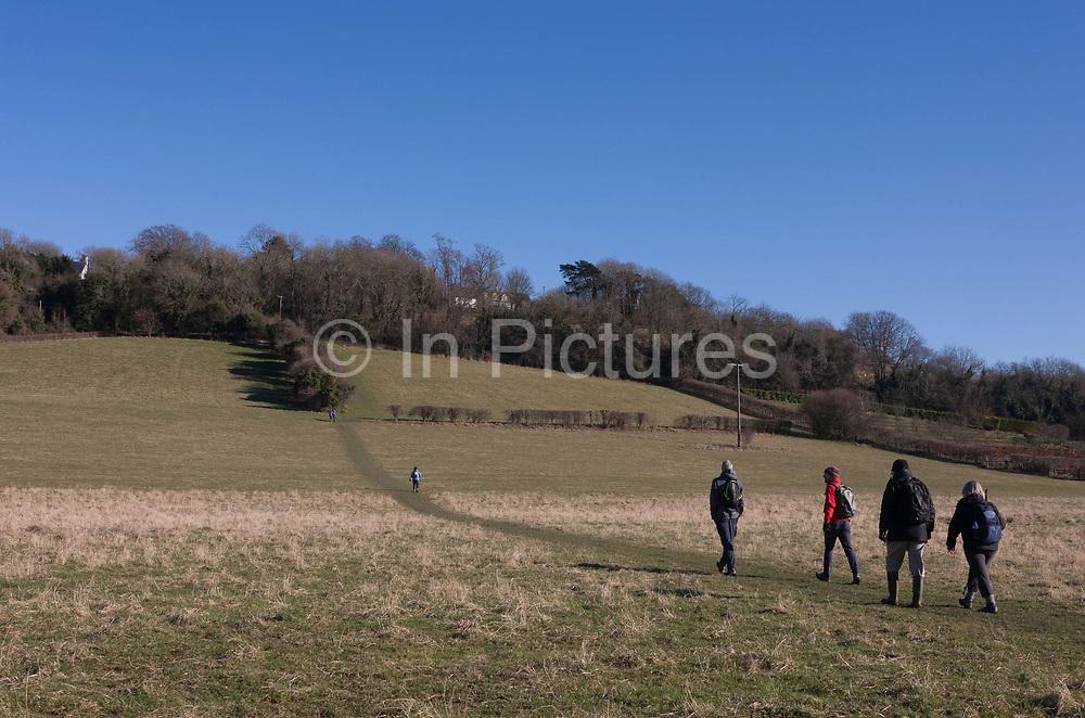Friends in a community walking group climb an escarpment while enjoy winter sunshine, on 25th February 2018, near Cudham, Kent, England.
