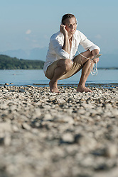 Mature man sitting at lakeside and listening to music with headphones, Bavaria, Germany