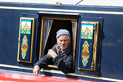 © Licensed to London News Pictures. 04/05/2019. London, UK. A man looks outside of his boat window during the annual Canalway Cavalcade festival in Little Venice canals in West London. <br /> Inland Waterways Association's (IWA) annual gathering of over 100 decorated canal boats with bunting and flags at the annual Canalway Cavalcade festival in Little Venice canals in West London. The festival runs over the May bank holiday weekend which has been taking place since 1983. Photo credit: Dinendra Haria/LNP