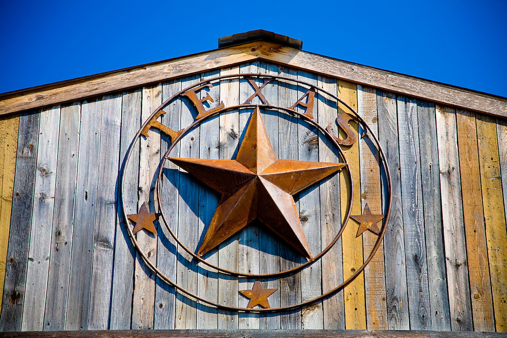 A wrought iron lone star hangs on a the front of a barn in the Texas Hill Country.
