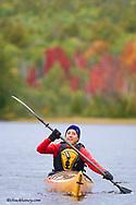 Sea kayaker on Lake Manganese duriing peak fall colors near Copper Harbor Michigan model released
