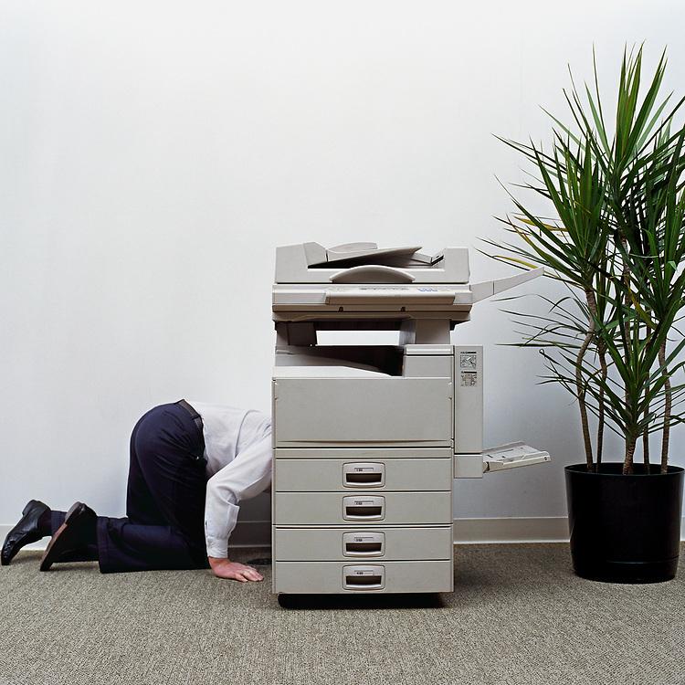60's Businessman kneeling beside photocopier, side view