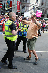 © Licensed to London News Pictures. 27/06/2015. London, UK. A protester tries to hold up the Pride in London parade and is later detained for breach of the peace and the possible assault of a police officer. Photo credit: Bettina Strenske/LNP