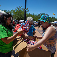Keely Johns, left, and Omar Jawad, right hand out free American Flags and pinwheels at the Fourth of July Celebration at the McKinley County Courthouse Square in downtown Gallup on Thursday.