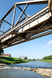 Man fishing underneath bridge on Trinity River near Trinity Trails, Fort Worth, Texas, USA.
