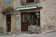Racing bicycle leaning outside Le Recantou cafe, and ice cream shop. Scene in the medieval village of Lagrasse, Languedoc-Roussillon, France.