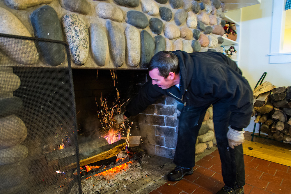An employee of Bay Cliff Health Camp builds a fire in a stone fireplace during the Michigan DNR Becoming an Outdoors Woman program.